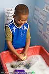 Education Preschool 4-5 year olds water table boy wearing smock playing in sudsy water vertical