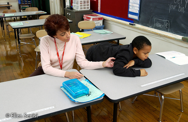 MR / Schenectady, NY.Yates Arts in Education Magnet School, Grade Two.Resource reading teacher tries to encourage boy (7, African-American) to participate in classroom activity..MR: Ste7 Hul1.© Ellen B. Senisi