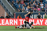 FOXBOROUGH, MA - JULY 25: Victor Wanyama #2 of CF Montreal tackles Tommy McNamara #26 of New England Revolution during a game between CF Montreal and New England Revolution at Gillette Stadium on July 25, 2021 in Foxborough, Massachusetts.