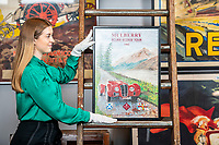BNPS.co.uk (01202 558833)<br /> Pic: MaxWillcock/BNPS<br /> <br /> Pictured: Sale Coordinator Lulu Randall with a Mulberry Ecurie Ecosse Tour 1992 advertising poster, in the Dreweatts Donnington Priory saleroom.<br /> <br /> A glamorous collection of early French motorsport posters has emerged for sale with a British auction house for £25,000.<br /> <br /> The earliest examples date from 1900 showing well-heeled Parisians chauffeured in vintage cars on the capital's streets.<br /> <br /> The vehicles are flanked by marching bands with passengers in their finest clothes to reinforce the element of prestige.<br /> <br /> There is a striking 1902 French poster of a British Mulberry car in the Scottish Highlands, while another celebrates the 1934 Grand Parade Vichy.