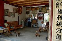 Two men watching television inside their home, Fuli Village, Guangxi, China.