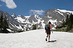 Woman hiking on snowfield with Navajo and Apache Peaks  behind in the Indian Peaks Wilderness Area west of Boulder, Colorado, USA Private photo tours to Indian Peaks. .  John leads private photo tours in Boulder and throughout Colorado. Year-round.