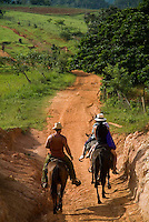 Family horseback riding in the countryside along with their Cuban guide, Vinales valley, Cuba.