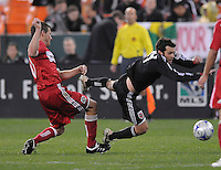 DC United midfielder Ben Olsen (14) being tackled by Chicago Fire forward Brian McBride (20) Chicago Fire tied DC United 1-1 at  RFK Stadium, Saturday March 28, 2009.