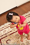16 month old toddler girl at home pretend play talking on telephone gesturing