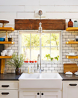 The kitchen features custom cabinetry topped with quartz countertops and complementary subway tile with black grout. Open wooden shelves provide storage.
