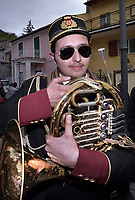 """A musician from the Cocullo band.The feast of snakes. Process dedicated to the Saint Dominic, in the streets of Cocullo, in the Abruzzo region, Italy on May 1, 2019.<br /> <br /> <br /> <br /> The St. Domenico's procession in Cocullo, central Italy. Every year on the first  of May, snakes are placed onto the statue of St. Domenico and then the statue is carried in a procession through the town. St. Domenico is believed to be the patron saint for people who have been bitten by snakes:<br /> <br /> Italy, Cocullo, in the Province of L'A...quila, is at 870 meters a.s.l., along the railway line connecting Sulmona to Rome. The village rises alongside Mount Luparo (1327 meters) """"The valley opening in front of the village is surrounded by bare rocks, while on the other side, to the south, snow-capped mountain crests follow one after the other...""""<br /> San Domenico Abate lived in the 10th and 11th centuries AD. Born in Foligno, in the Umbria region, he started his pilgrimages, preaching and ascetic practices in Central Italy, making miracles recorded by the word-of-mouth tradition. He died on 22 January 1031 and was buried in Sora.<br /> <br /> Cocullo snake charmers are over with their snake hunting. They proceeded through the During the procession on the first in May, before the snakes are placed all over the statue of St. Dominick, they will be fed with milk kept in containers with crusca. It is the snake that, most of all other elements, expresses an ancestral myth: the unknown aspect and unpredictability of the natural environment with man's innate need to achieve the dominance on his own habitat. <br /> <br /> Snakes and wolves were the emblems of Italic peoples like the Marsians and Irpinians. Some areas in Abruzzo, especially in the Sagittario valley, were under the menace of wolves and snakes, which for the local populations represented the uncertainty and anxiety of their existence that, together with the precariousness and hardships of life, were almost unbearab"""