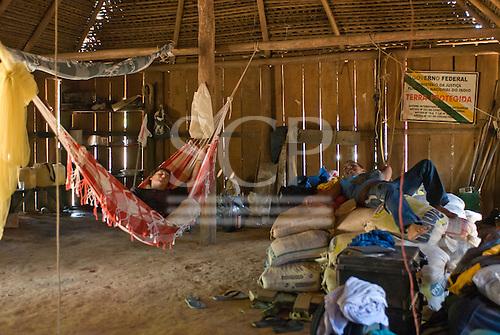 Mato Grosso State, Brazil. Aldeia Metuktire (Kayapo). Patrick Cunningham asleep in Waiwai's house, with Gilson.