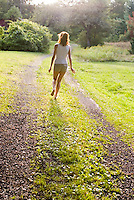 Red haired woman walking along grassy road<br />