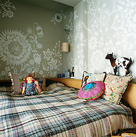 The bedroom has a hand painted floral design on the walls and the bed has a check pattern bed cover. Embroidered cushions are scattered on the bed