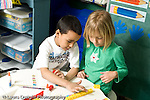 Education Elementary school Grade 1 mathematics boy and girl making columns of colored cubes and comparing them to rows of glued paper squares hands on learning horizontal