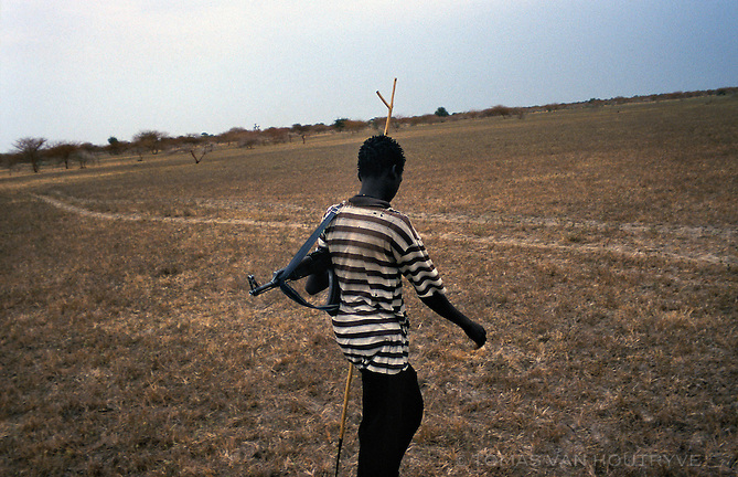 John Shuol, a young Nuer tribesman, carries his Kalashnikov AK-47 as he walks from the village of Yiditin towards Walgak in the Upper Nile region of South Sudan on Nov. 23, 2004. After more than 20 years of devastating civil war, most men and even boys carry arms in South Sudan. The population remains vulnerable to disease, stunted developement, and persistent tribal and militia fighting.