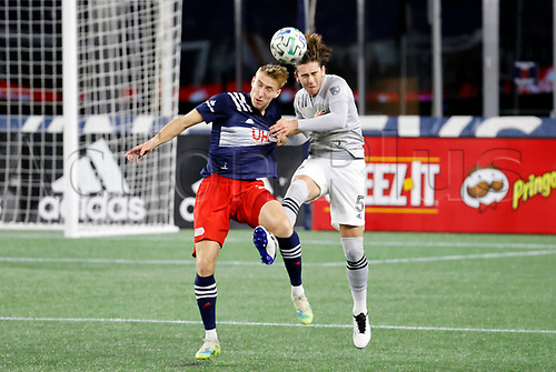 20th November 2020; Foxborough, MA, USA;  Montreal Impact defender Luis Binks heads the ball away from New England Revolution forward Adam Buksa during the MLS Cup Play-In game between the New England Revolution and the Montreal Impact