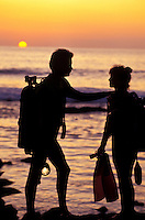 Couple with scuba gear coming out of ocean at sunset, Kona, Big Island of Hawaii