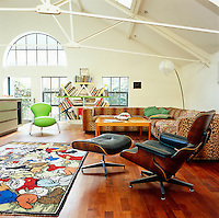 The main living area in the converted postal sorting office is furnished with a Cappellini sofa upholstered in leopard-print material, a vintage Swedish coffee table and an Eames lounge chair