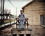 """To pose this pair of fine hounds atop their doghouse, the photographer has enlisted the services of a boy in a crooked-buttoned cardigan sweater. Some of the most captivating photographs are those where children are center-stage. In spite of their often tattered clothing, children are never depicted as downtrodden or """"less than"""". Rather, they have a special nobility."""