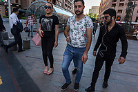 """Armenia. Yerevan. Town center. Lilit Martirosyan stands in the middle of a group of men on Northern Avenue. She waits to cross the Hin Yerevantsi Street and carries a pink purse on her right arm. She is a transgender woman and a civil rights activist fighting for the rights of trans people in Armenia. On her right arm, a tattoo with the words """" All Equal All Different"""". Lilit Martirosyan is the founder and the president of the NGO called """"Right Side"""", founded in 2016 to defend and fight for the rights of the trans community in Armenia. She became on April 5th 2019 the first member of her country's lesbian, gay, bisexual, transgender and intersex (LGBTI) community to deliver a speech on the parliamentary podium, speaking out against discrimination at a session of its committee on human rights. A trans woman (sometimes trans-woman or transwoman) is a woman who was assigned male at birth. Trans women may experience gender dysphoria and may transition; this process commonly includes hormone replacement therapy and sometimes sex reassignment surgery, which can bring immense relief and even resolve gender dysphoria entirely. Yerevan, sometimes spelled Erevan, is the capital and largest city of Armenia. Northern Avenue is a pedestrian avenue in Yerevan,  opened in 2007. It is in the central Kentron district and links Abovyan Street with Freedom Square on Tumanyan street. It is 450 metres long and 27 metres wide. Located in downtown Yerevan, the avenue is mainly home to luxurious residential buildings, high-end branded shops, commercial offices, coffee shops, hotels, restaurants, and nightclubs. 1.10.2019 © 2019 Didier Ruef"""