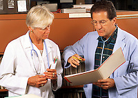 Male and female medical doctors in consultation, conferring over a chart.