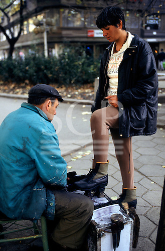 Sofia, Bulgaria. Shoe-shine man in dirty coat polishing boots of a woman.