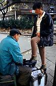 Sofia, Bulgaria. Shoe-shine man in dirty coat polishing boots of a woman.