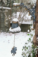Snow on garden bell ornament in winter hanging from tree