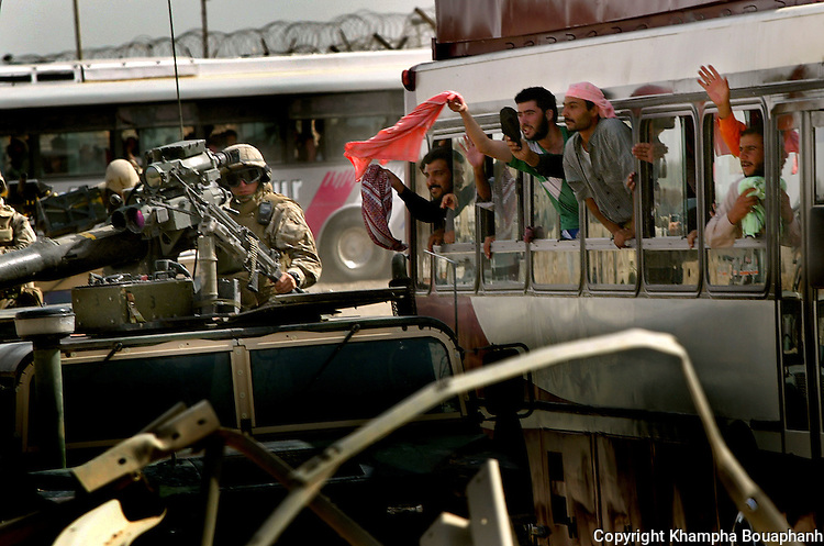 Iraqi prisoners wave to love ones as they leave the gates of Abu Ghraib prison on May 21, 2004.   Reports of abuse at the prison resulted in the suspension of the commanding general and charges brought up against several U.S. soldiers.  (photo by Khampha Bouaphanh)