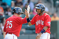 Second baseman Wendell Rijo (11) of the Greenville Drive is congratulated by Tim Roberson after scoring a run in a game against the Augusta GreenJackets on Sunday, July 13, 2014, at Fluor Field at the West End in Greenville, South Carolina. Rijo is the No. 18 prospect of the Boston Red Sox, according to Baseball America. Greenville won, 8-5. (Tom Priddy/Four Seam Images)