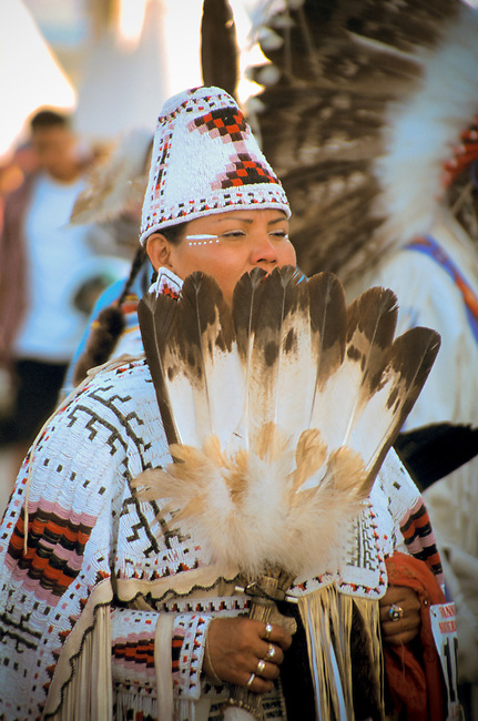 Woman dressed in fully beaded cylinder hat and cape holds up an eagle wing dance fan during the Blackfeet Indian Days Festival, Browning Montana