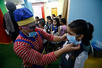 A clown hired by a local kindergarten instructs children how to wear a face mask during an awareness session about COVID-19 coronavirus disease at the premises in Gaza City on August 10, 2020, as education facilities in the Palestinian enclave re-opened for the new 2020-2021 academic year following an easing of pandemic restrictions. Photo by Osama Baba