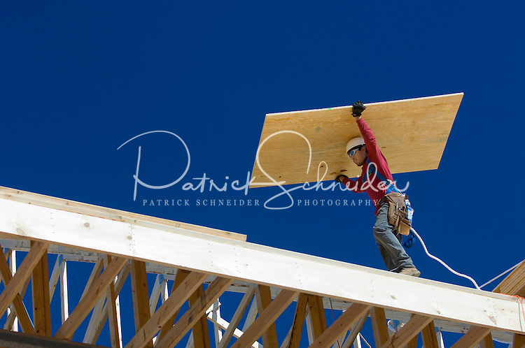 02/22/07:  A construction worker prepares to attach plywood sheets to create a new roof during expansion/construction of a Charlotte-area shopping center. Charlotte, NC, is one of the country's fastest-growing cities. ..By Patrick Schneider- Patrick Schneider Photography.