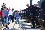 Davis Weist,6, high-fives his dad, Trent, who is a K-9 officer Portland Police Bureau, before a public tribute honoring the service of the  Canine, Mick, at Hillsboro Stadium.<br /> Photo by Jaime Valdez