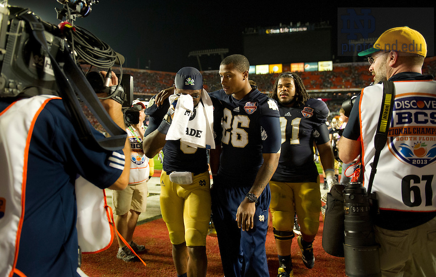 Jan. 7, 2013; Running back Theo Riddick is consoled by  teammate Jamoris Slaughter as they walk off the field together after the 2013 BCS National Championship in Miami, Florida. Alabama defeated Notre Dame 42 to 14. Photo by Barbara Johnston/University of Notre Dame
