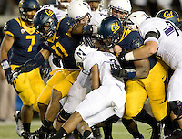 California defenders tackle Venric Mark of Northwestern during the game at Memorial Stadium in Berkeley, California on August 31st, 2013.  Northwestern defeated CAL, 44-30.