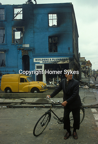 Brixton, London, 1981.<br /> An elderly Brixton residents out on his bike surveys the scene of the previous night rioting.  Twenty eight building were burnt out and hundred were looted.