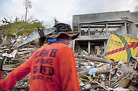 Philippines. Province Leyte. Tacloban. A man cleans waste from the street. A lonely boy among houses's rubble. Typhoon Haiyan, known as Typhoon Yolanda in the Philippines, was an exceptionally powerful tropical cyclone that devastated the Philippines. Haiyan is also the strongest storm recorded at landfall in terms of wind speed. Typhoon Haiyan's casualties and destructions occured during a powerful storm surge, an offshore rise of water associated with a low pressure weather system. Storm surges are caused primarily by high winds pushing on the ocean's surface. The wind causes the water to pile up higher than the ordinary sea level. 1.12.13 © 2013 Didier Ruef