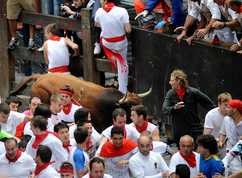 Participants run in front of Cebada Gago's bulls during the third San Fermin Festival bull run, on July 9, 2012, in Pamplona, northern Spain. The festival is a symbol of Spanish culture that attracts thousands of tourists to watch the bull runs despite heavy condemnation from animal rights groups. AFP PHOTO / ANDER GILLENEA
