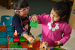 Education Preschool 4 year olds two girl building together with colored plastic magnetic blocks, talking and planning
