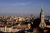 Bratislava, Slovakia. View over the city; St Martin Coronation cathedral church spire; smoking industrial chimney.
