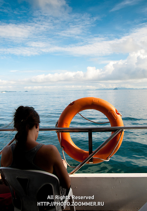 Woman on a ferry near orange ring lifebuoy and azure sea