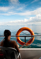 Woman on a ferry near orange ring lifebuoy and azure sea
