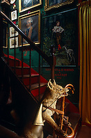 A stuffed fox with a hunting bugle hanging from its neck stands by the foot of the staircase and serves as an umbrella stand