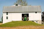 White bank barn with John Deere tractor.