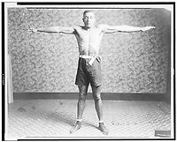 Boxer Tut Jackson clothed in boxing trunks, full-length portrait, standing, facing front, with his arms extended out from his sides, showing his reach, 1922