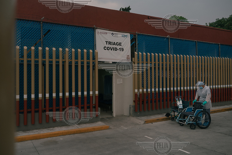 A hospital worker waits with a wheelchair outside the COVID-19 triage area at the General Hospital of Mexico.