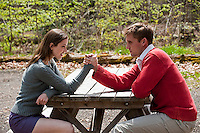 Young couple arm wrestling sitting at picnic table