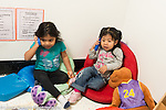 Education preschool 3 year olds two girls pretend play talking on telephones made from blocks (manipulatives)