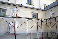 Switzerland. Canton of Ticino. Val di Blenio (Blenio valley). Aquila. Three painters are cleaning the wall of a catholic church before starting to paint it. © 2006 Didier Ruef