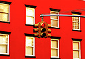 Red Traffic light against red building in Soho in  in New York USA Credit Geraint Lewis