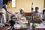 Ashutosh Sharma of Amarrass records pulls the microphone closer to 75-year-old Manganiyar artist, Saqar Khan while he sings and plays his Kamancha (music instrument) with his son, Firoze Khan (right) inside his house in Hamira village of Jaiselmer district in Rajasthan, India. Photo: Sanjit Das/Panos