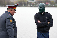 Moscow, Russia, 01/05/2010..A policeman moves a masked Russian fascist at a demonstration in central Moscow. A variety of political groups took to the streets on the traditional Russian Mayday holiday.